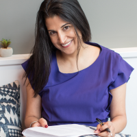 Dr. Rupa Valdez in a purple blouse, book in hand, smiling.