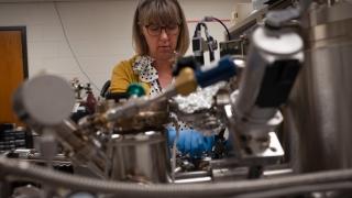 UVA Engineering researcher Catherine Dukes inserts vacuum tube into XPS machine