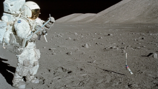 NASA astronaut Jack Schmitt rakes up rocks from the lunar surface during the last manned mission to the moon