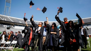 engineering students, dressed in black robes, toss their graduation caps in the air