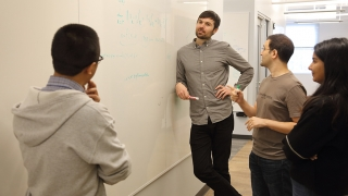 Cody Fleming with graduate students at whiteboard in Link Lab