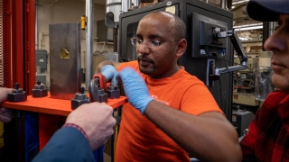 Amedebrahan Asfaw, a Ph.D. candidate at UVA Engineering's Department of Engineering Systems and Environment tightens the smart metal alloy strands in his earthquake dampening device.