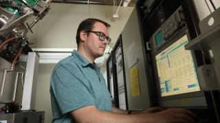 Jeroen Deijkers reviews data on screen next to direct vapor deposition chamber