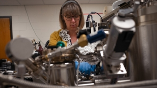 Catherine Dukes inserts a sample into an X-ray photoelectron spectrometer