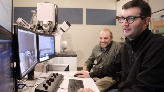 Zach Harris and Hoglund examine the microstructure of an additively manufactured polished steel sample