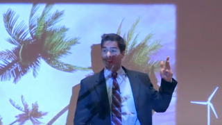 Carlos Noyes speaking in front of an image of palm trees.